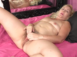 Small titted mature is toying her hairy pussy with a pink vibrator and moaning while cumming